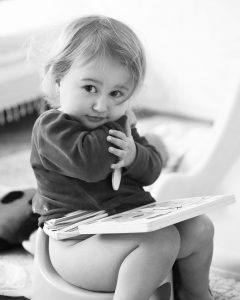 Little girl happily taking a wee on a potty