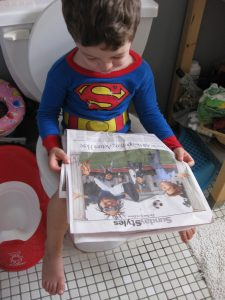 Toddler reading a newspaper on a toilet